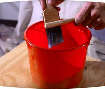 Une personne nettoyant un pinceau au-dessus d'un seau rouge