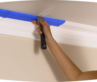 Person applying painters tape to ceiling trim