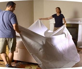 Two people covering furniture with tarp in preparation for painting