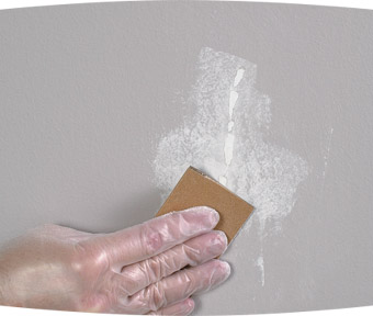 Person repairing crack in wall