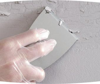 Person repairing peeling paint on wall
