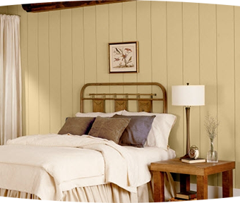 Paneled bedroom with white comforter covered bed and table with lamp on it
