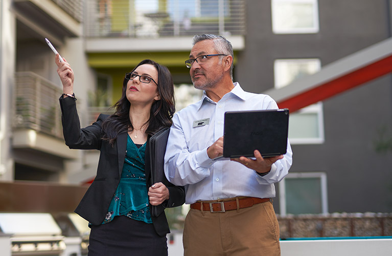 A small image of a Property Manager showing a BEHR Rep a multi-family apartment complex. The property manager is pointing at something while the BEHR PRO Rep is looking at what she is pointing and taking notes on a laptop.