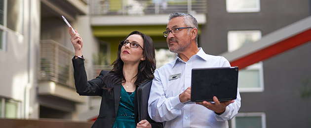 A large image of a Property Manager showing a BEHR Rep a multi-family apartment complex. The property manager is pointing at something while the BEHR PRO Rep is looking at what she is pointing and taking notes on a laptop.