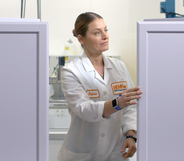A Behr employee in a laboratory coat inspecting to see if paint is dry.