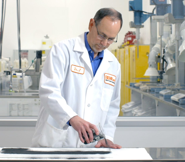 A Behr employee in a laboratory coat putting dirt on a surface to test.