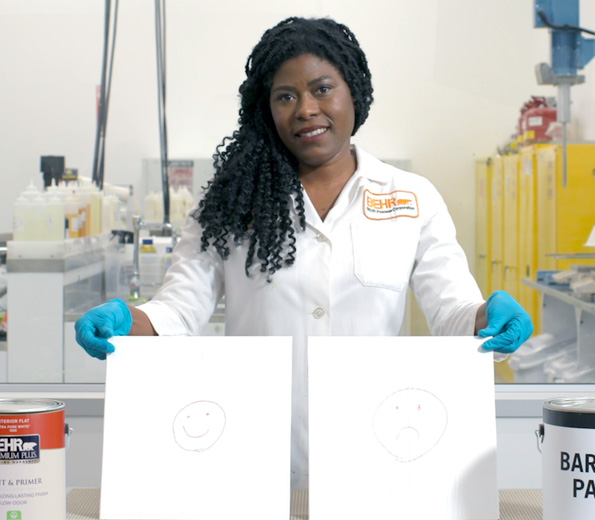 A Behr employee in a laboratory coat holding 2 boards.