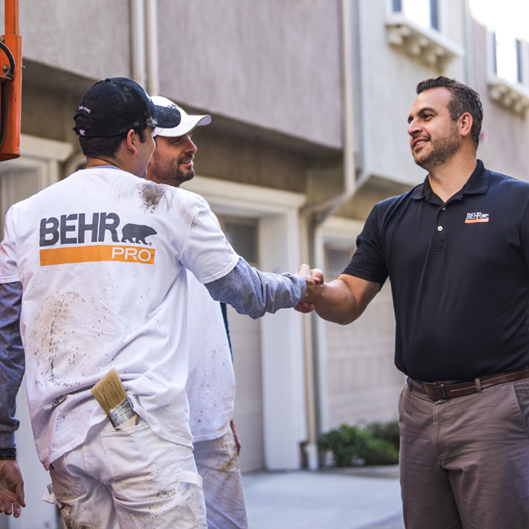 A mobile view of a BEHR Rep shaking hands with on of the 2 Pro Painters. In the background is a multi-family condo units.