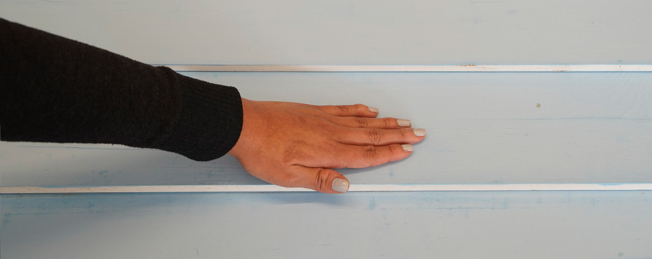 Hand checking chalkiness of painted wall, pass 4