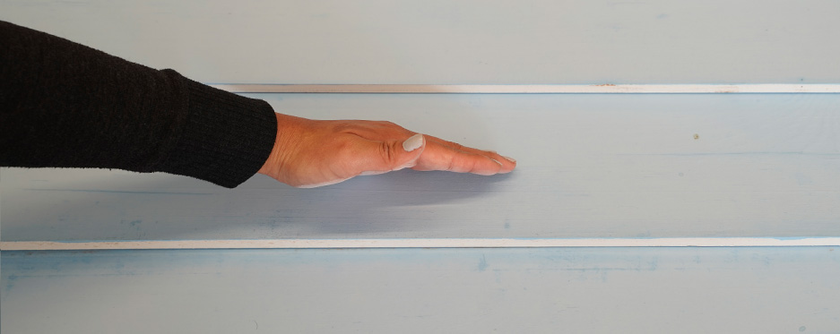 Hand checking chalkiness of painted wall, pass 6