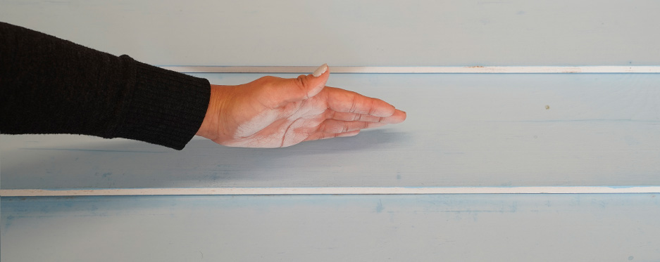 Hand checking chalkiness of painted wall, pass 7