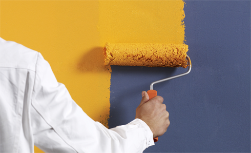 Person rolling yellow paint on a dark gray wall