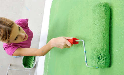 Woman in pink shirt rolling green paint on the wall