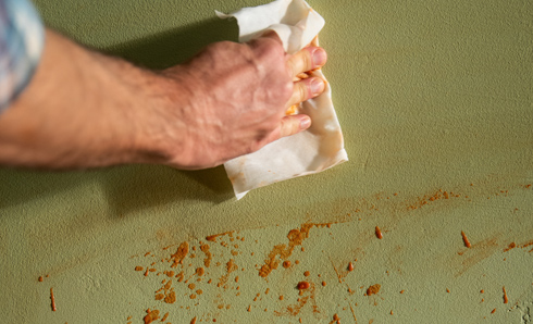 Person's hand holding a wet wipe and cleaning a food stain off the wall