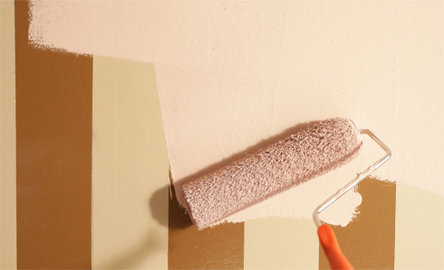 Paint roller painting tan color on a wall