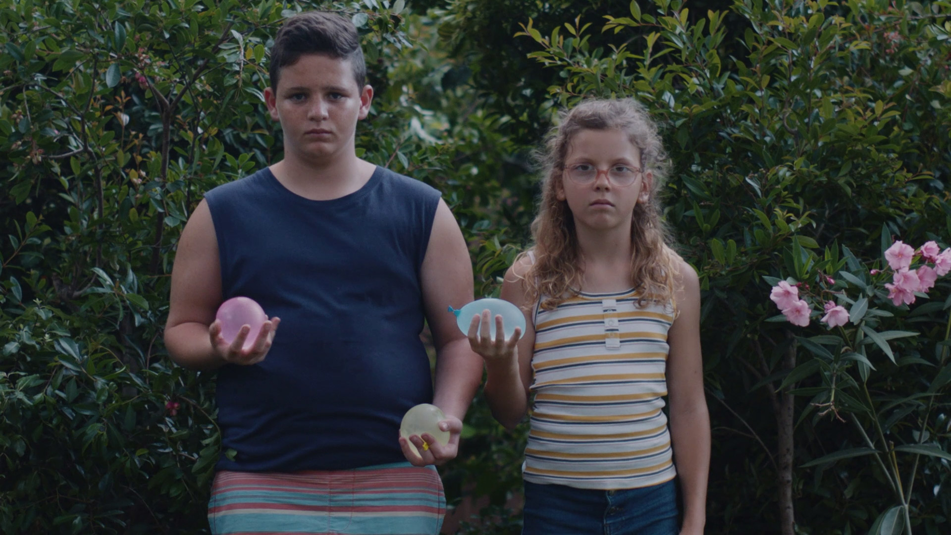 Young boy and girl holding water balloons in their hands