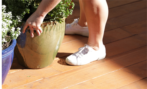 Person standing on deck about to pick up a flower pot