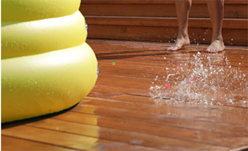 Person standing on a deck with water splashing off the deck