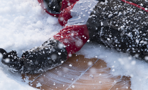 Child in black white and red jacket making a snow angel
