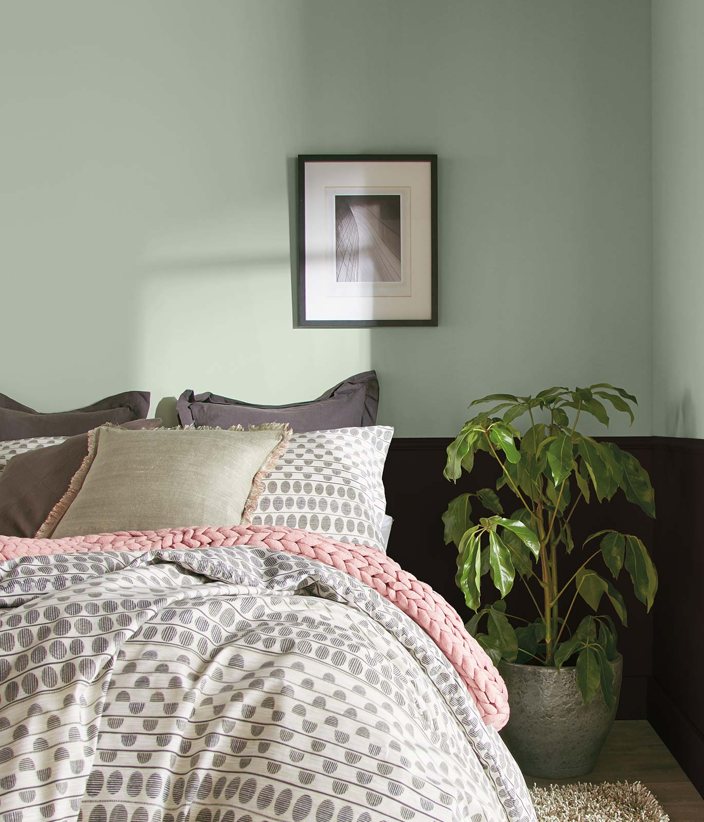 Tight crop of a bedroom with gray and white bedding. Upper half of the walls are painted in a light green. The bottom half is painted black. The feel of the room is calming.