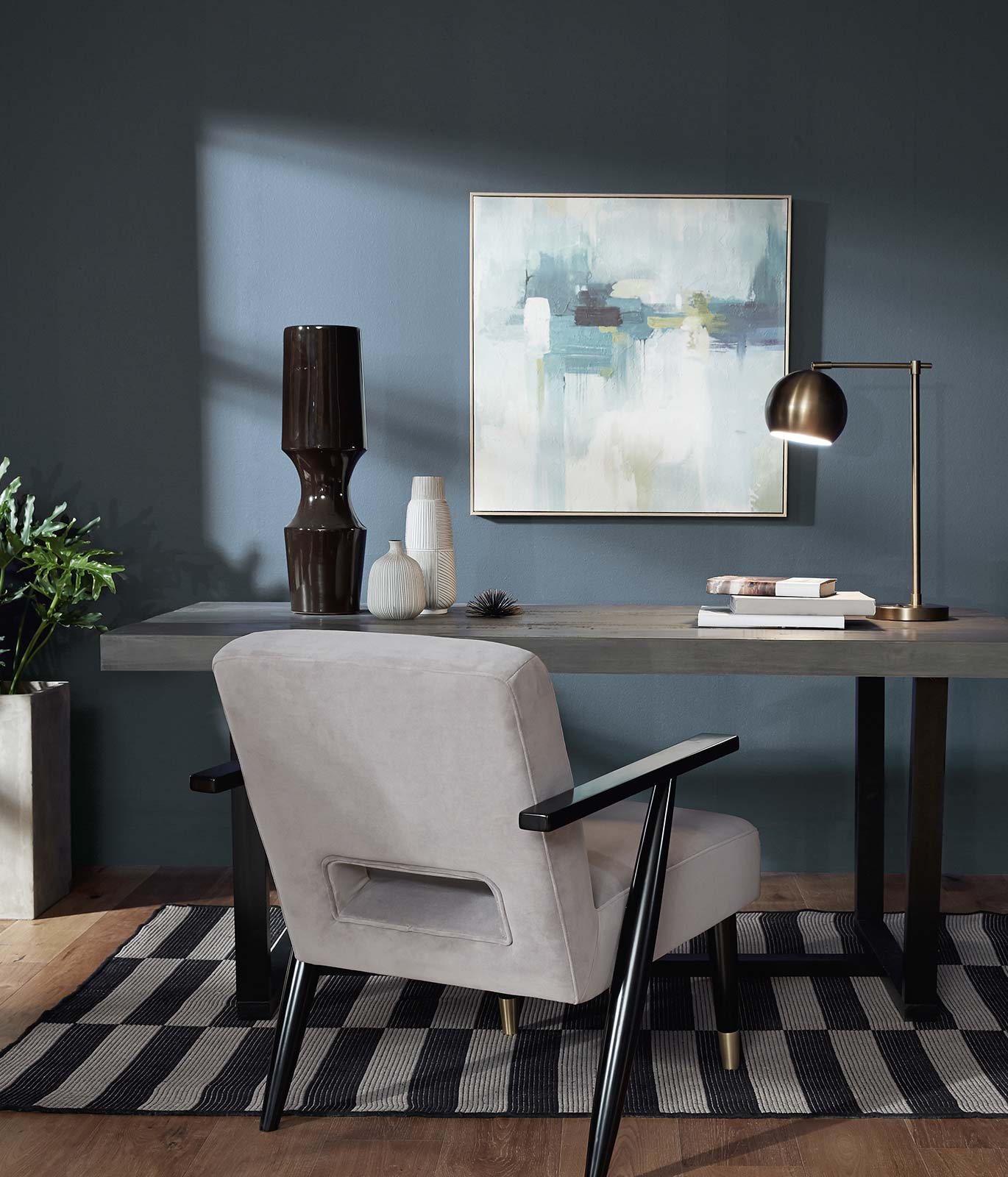 An office with a gray colored wood desk sitting against a wall painted in blue. There is a abstract painting hanging on the wall. The mood is relaxed and calm.