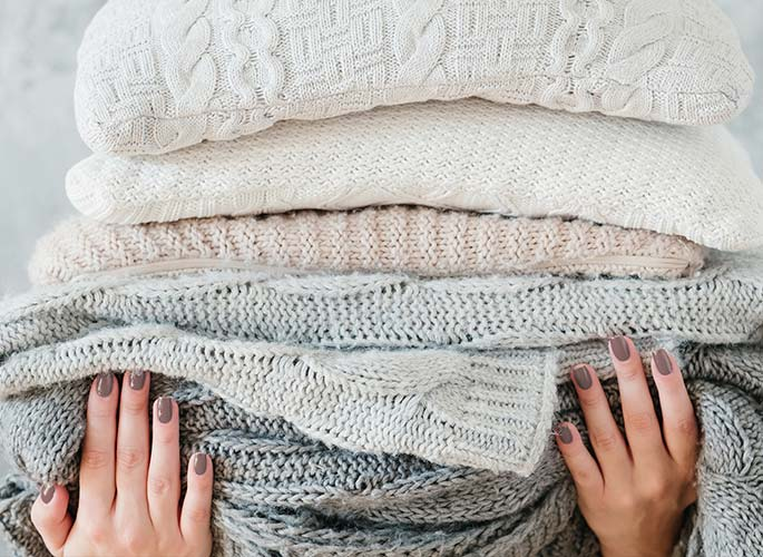 A stack of warm, cozy neutral colored sweaters.