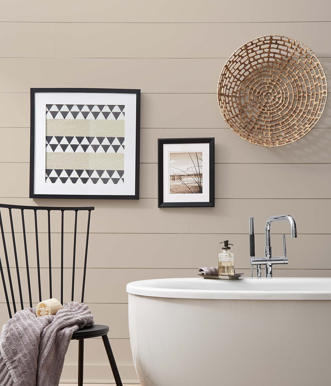 A bathroom painted in a beige color showing corner of a tub with a simple chair and blanket. Décor gives off a casual and comfortable feeling.