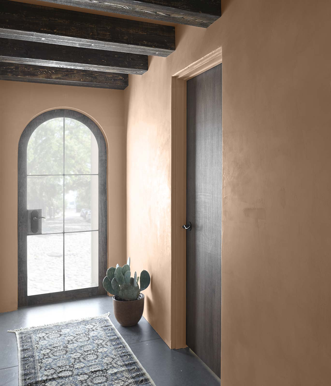 A comforting entry way with warm tan painted walls and dark brown colored wood trim.