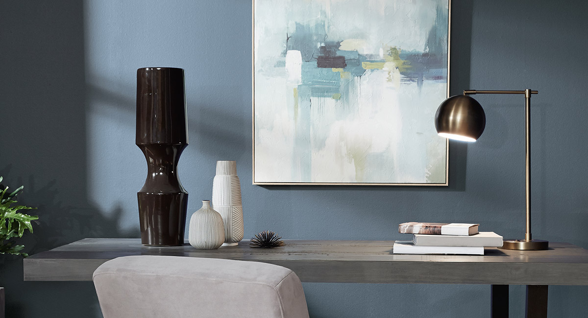 A calming office with a graycolored wood desk sitting against a wall painted in blue. There is a abstract painting hanging on the wall.