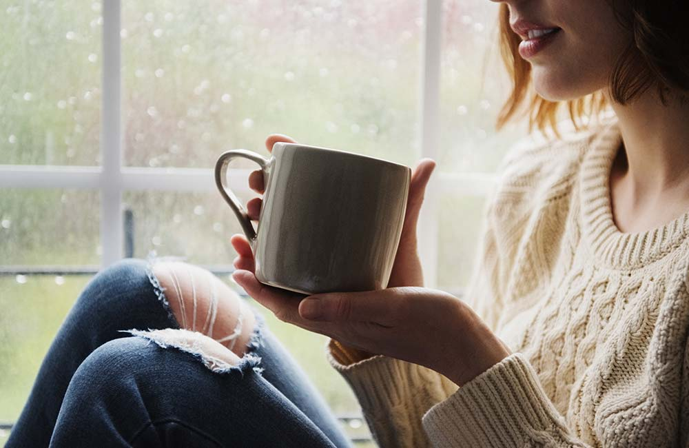 A woman sitting cozily by a window comforted by a warm cup of coffee. Outside is raining.