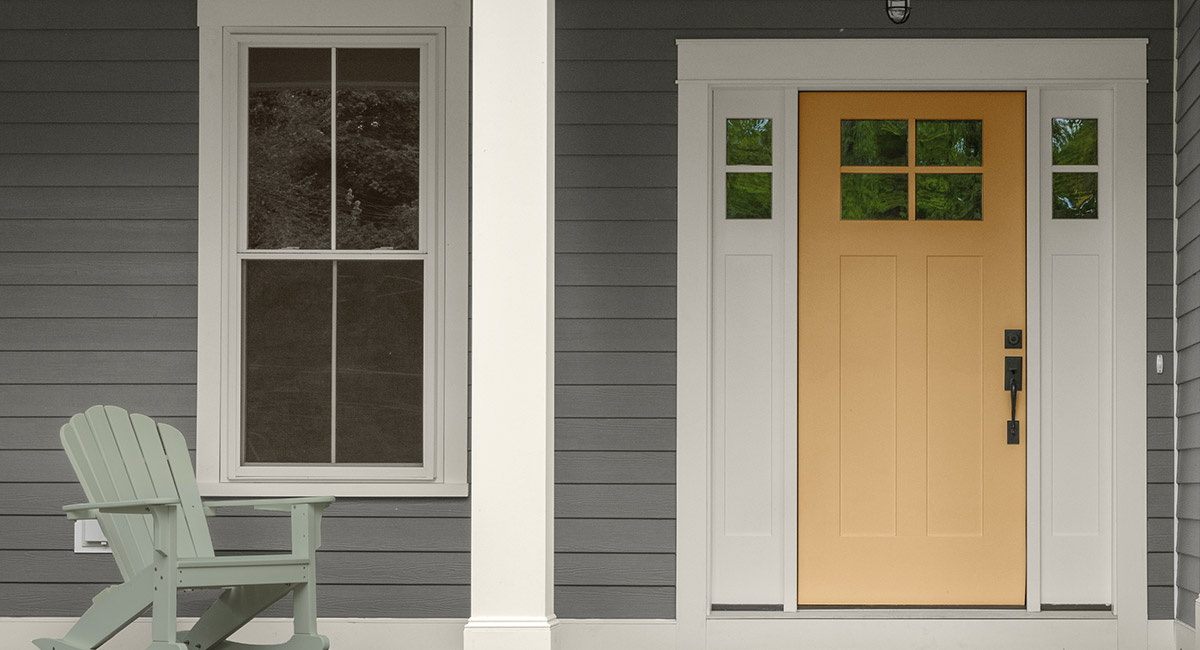 The front porch of a gray painted home with a yellow door and a green rocking chair. The mood is relaxed.