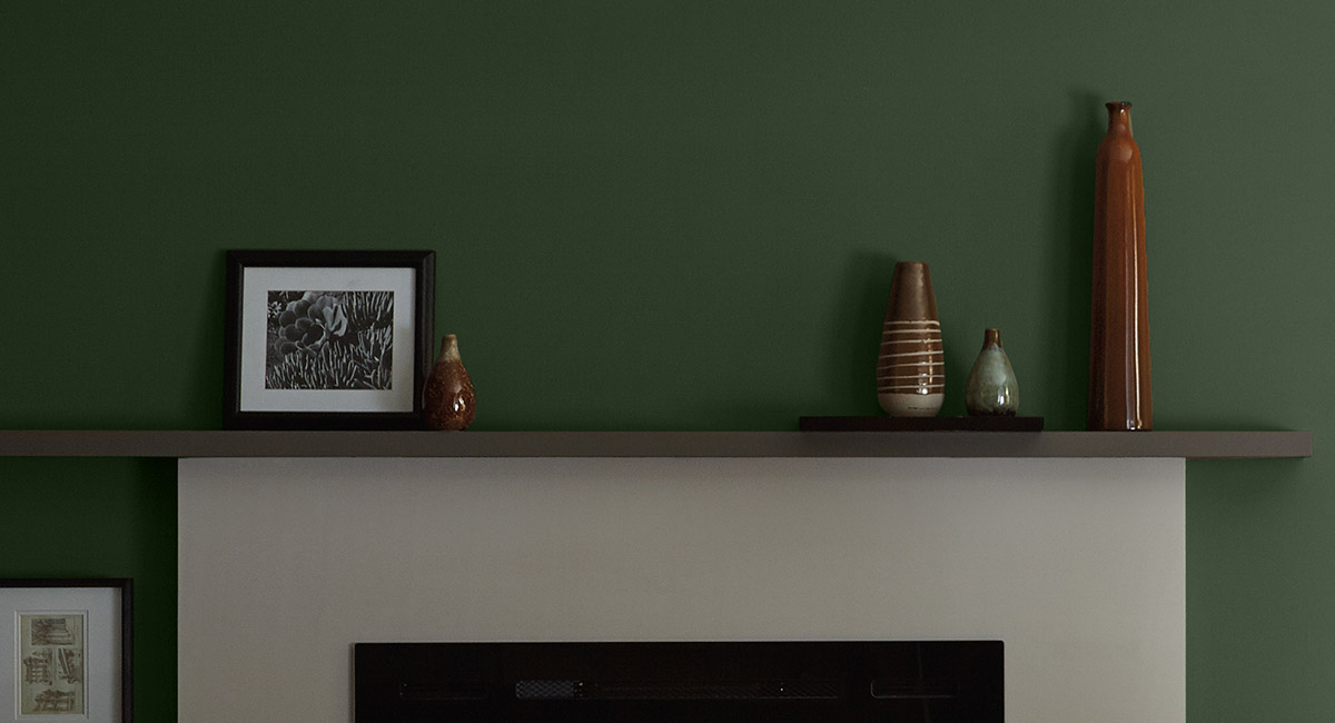 A white cement fireplace against a green painted wall. The mood is quiet and peaceful.