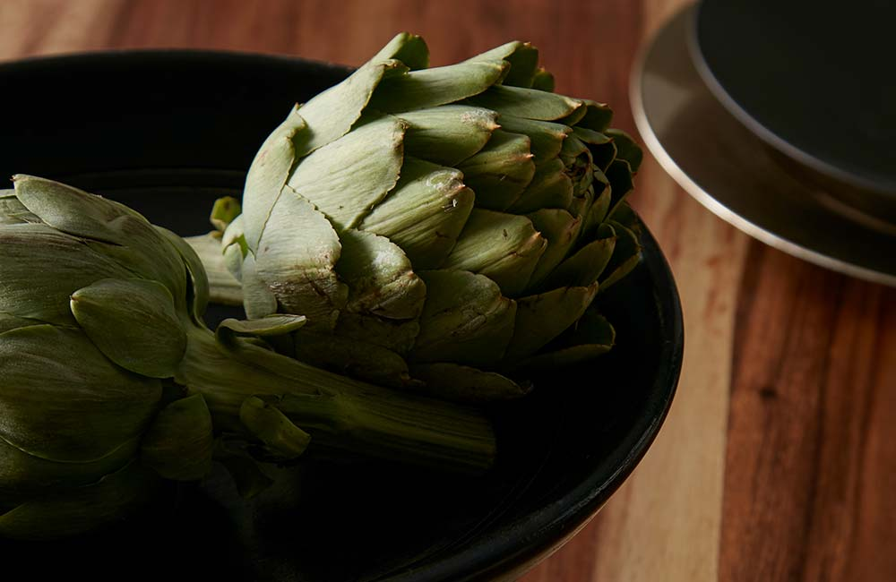 A bowl filled with untouched artichokes waiting to be cooked, the atmosphere is quiet and calm.