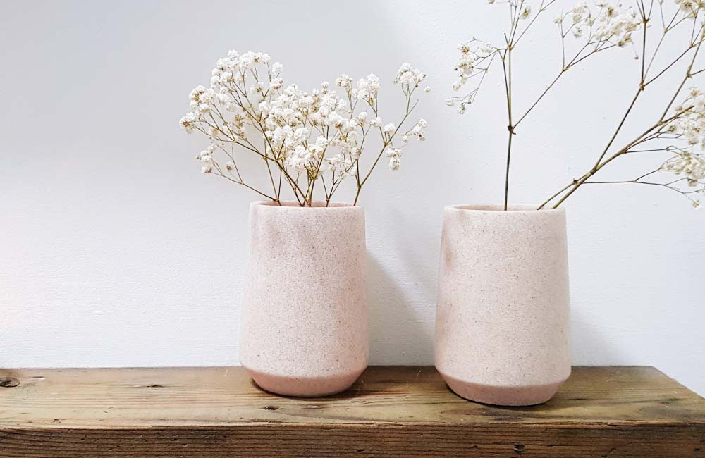 Two vases with white small flowers sitting on a wood shelf. Flowers in vase are soft and subtle.