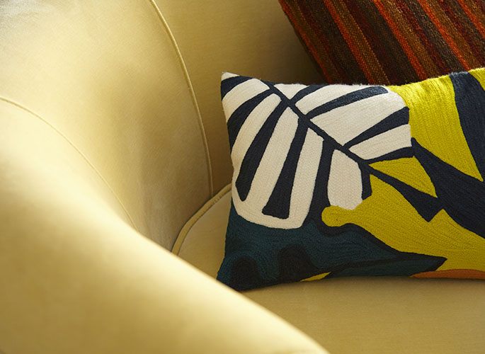 A tight crop of a yellow couch with bright yellow and navy blue abstract pattern on the pillows.
