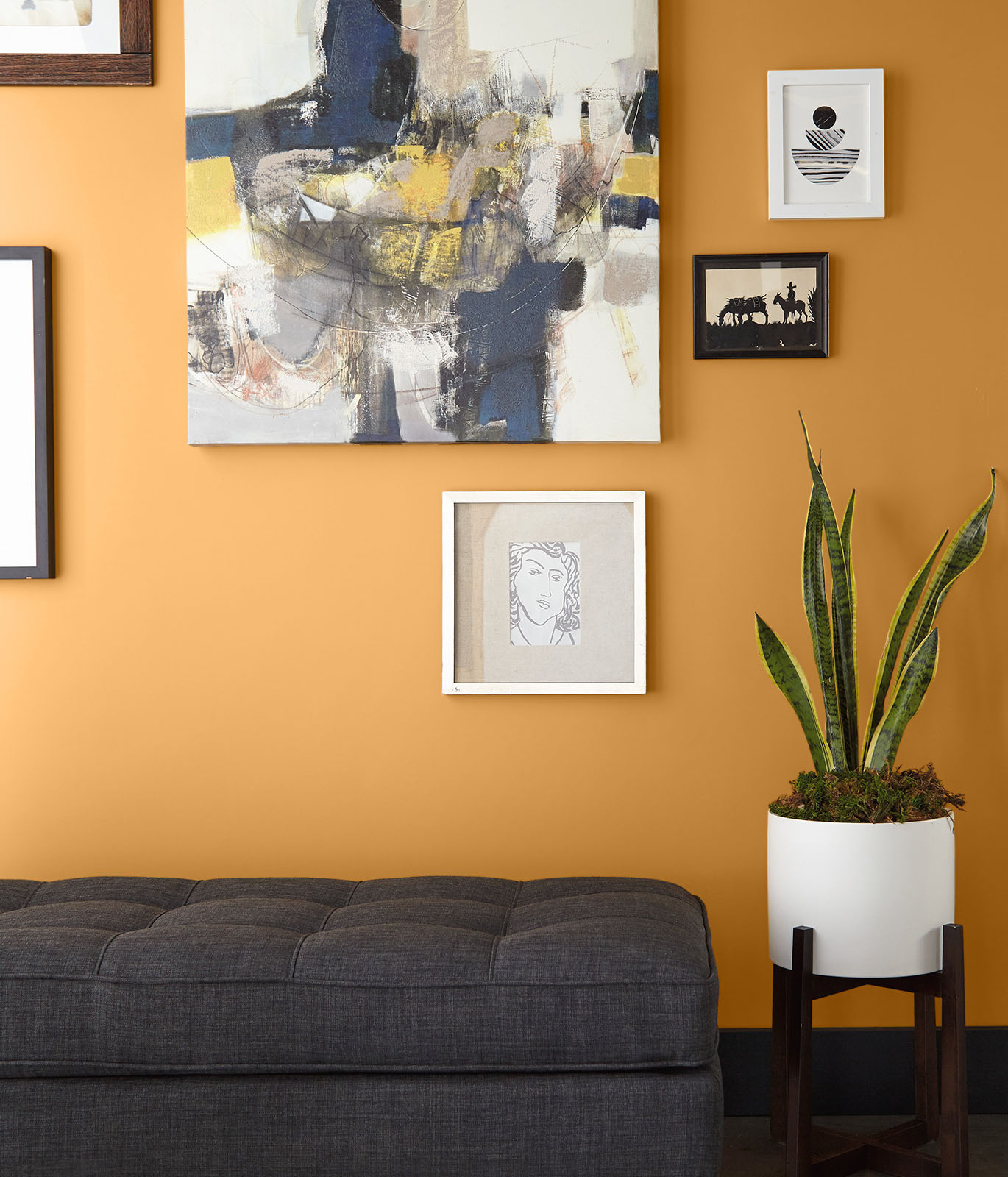 A living room painted in golden-yellow with a gray couch. The wall is filled with hanging art work. The room feels optimistic and bright.