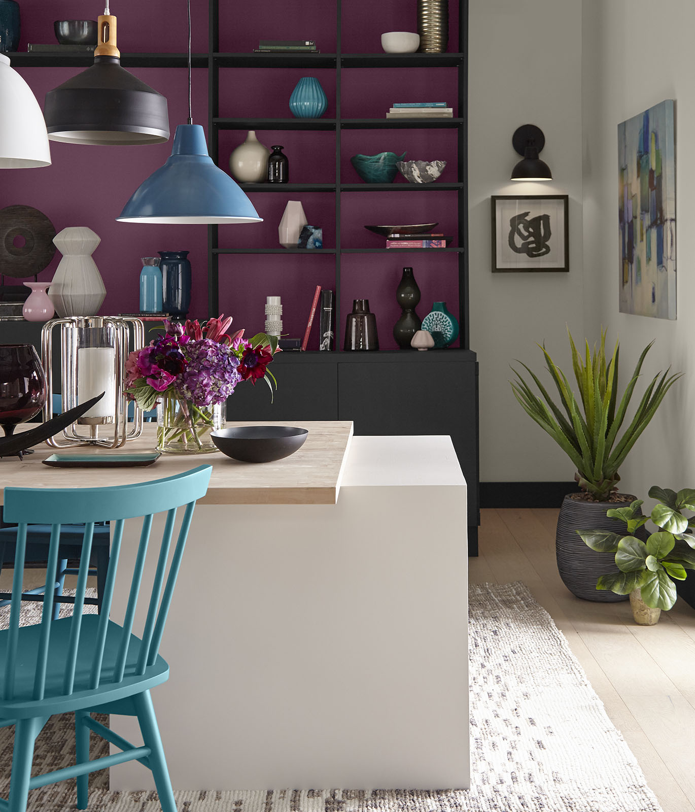 A dining room with a white and wood table in the foreground. In the background is a bookshelf painted a magenta color inside the shelves and black for the cabinet. The room gives off an optimistic vibe.