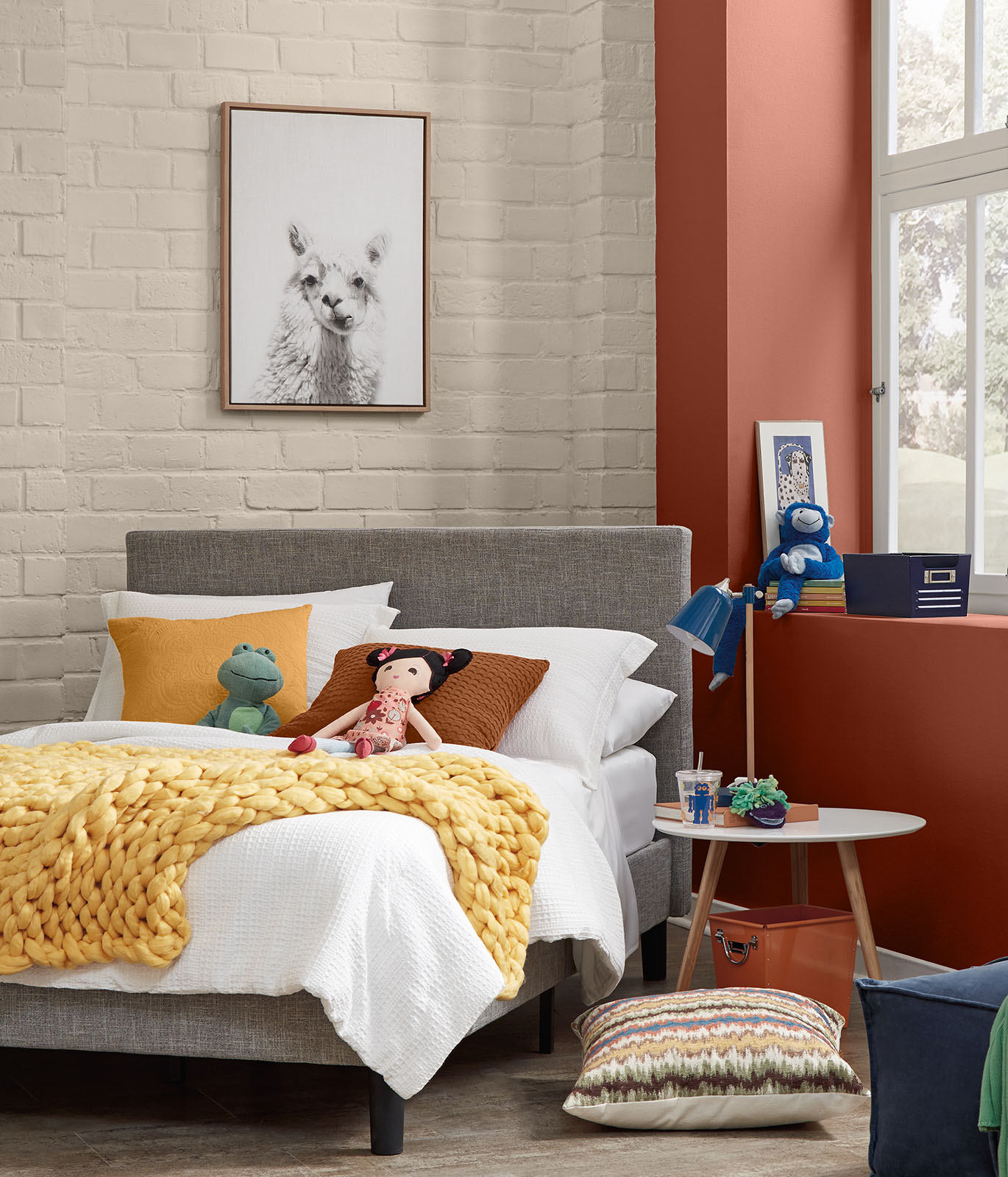 A child's bedroom with cream colored painted brick walls. The accent wall in painted in a dark orange color. The feeling of the room is cheerful.