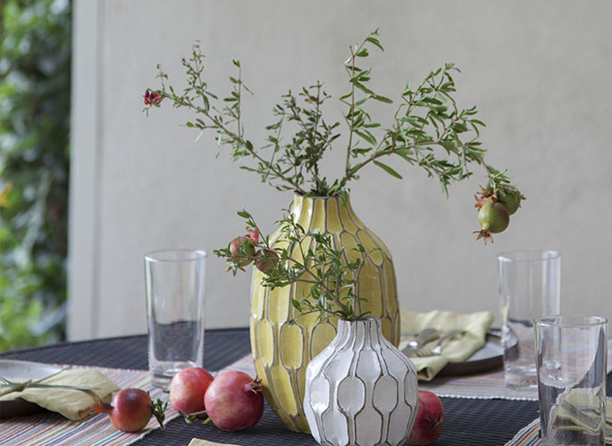 A tight crop showing a table sitting outside that is   dressed with white and yellow vases.
