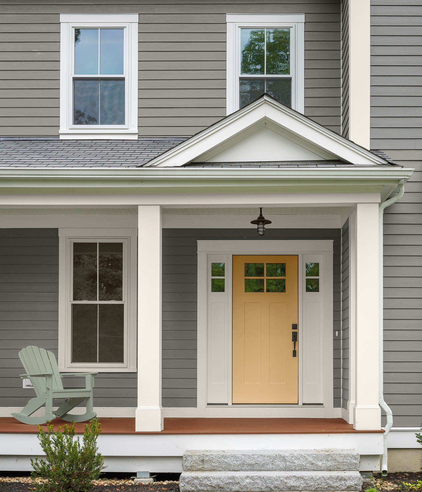 An exterior home painted in a gray color with a yellow front door.
