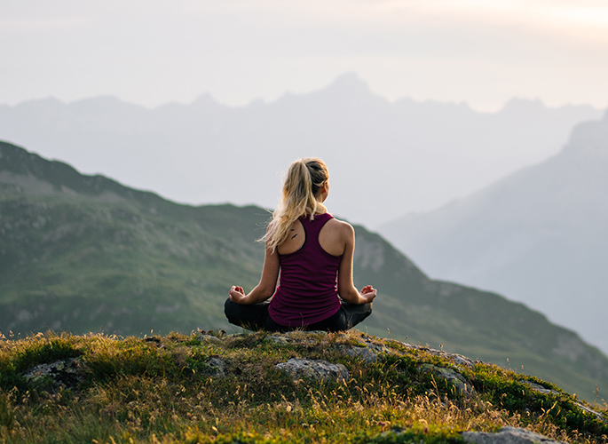 A woman siting on a flowered mountain top meditating. Her surroundings are of a quiet sky and mountains.
