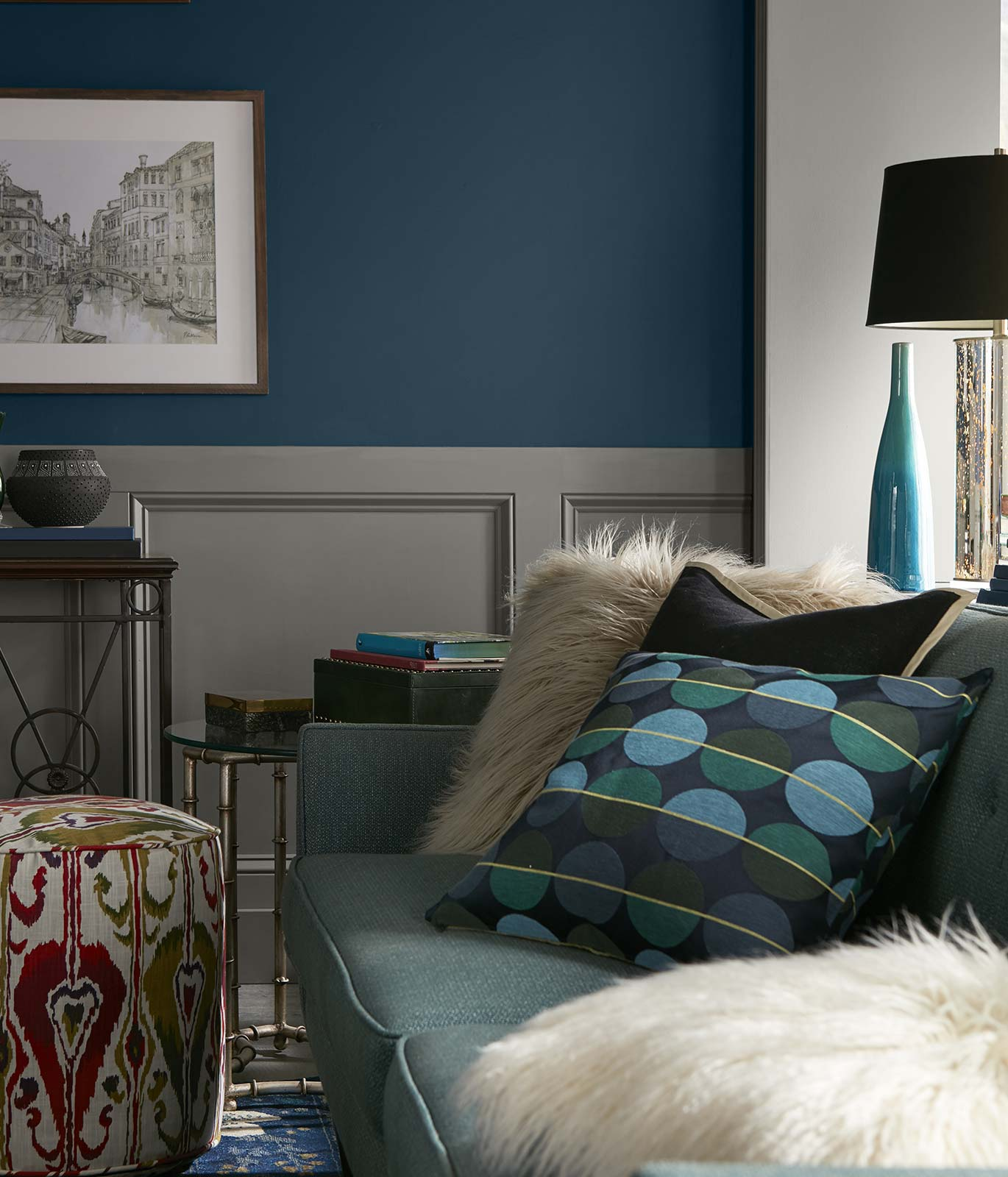 A tight crop of a living room with a light blue couch and darker blue painted walls. The mood is quiet and relaxed.