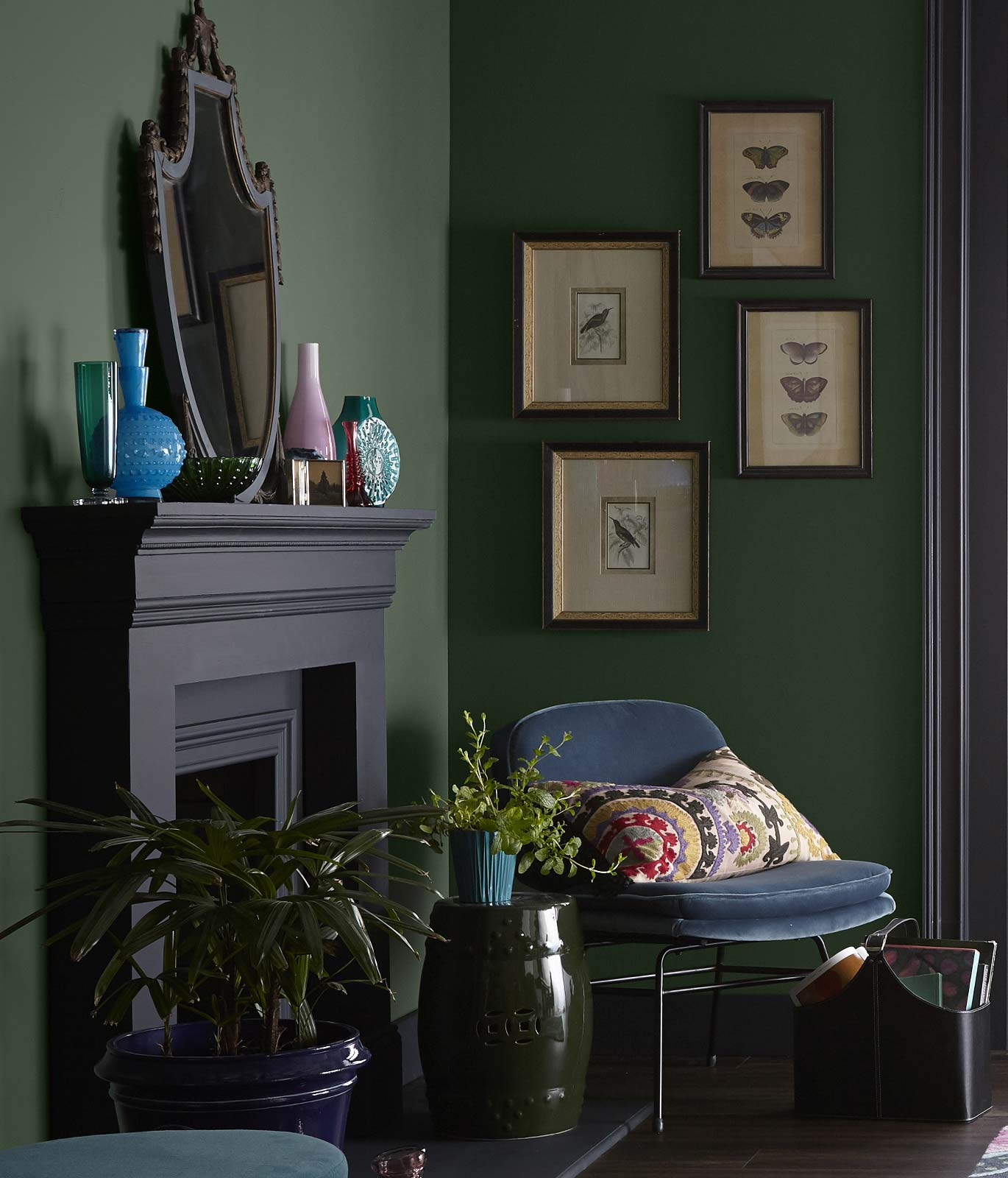 A quiet corner of a living room showing a black painted fireplace, a velvety chair in a blue color. The walls of the room are painted in a dark green color.